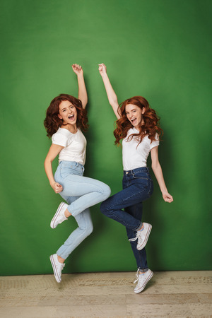 Full length photo of two joyous girls 20s with ginger hair in casual jeans smiling and jumping with raised arms isolated over green background