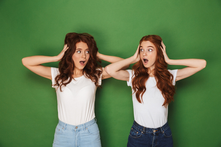 Portrait of two scared or uptight women with red hair in white t-shirts looking at each other and covering ears isolated over green background