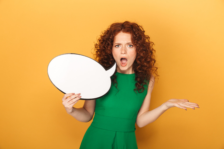 Portrait of an angry redhead woman in dress holding empty speech bubble isolated over yellow background