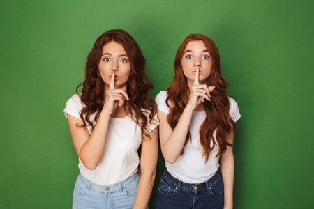 Shh! Portrait of two young redhead women 20s in casual wear looking at camera and holding index fingers on lips isolated over green background Фото со стока