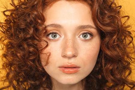 Close up portrait of a beautiful curly redhead woman looking at camera isolated over yellow background 스톡 콘텐츠