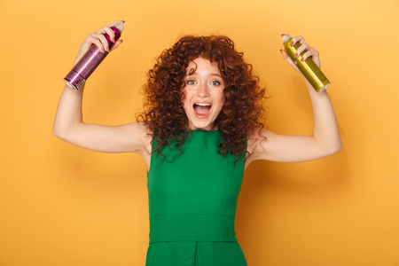 Portrait of an excited curly redhead woman holding two hair sprays isolated over yellow background
