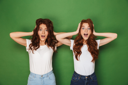 Portrait of two funny women with red hair in white t-shirts looking at camera and covering ears isolated over green background