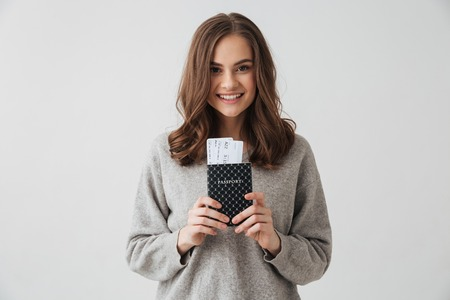Smiling brunette woman in sweater preparing to trip while holding passport with tickets and looking at the camera over grey background Stock Photo