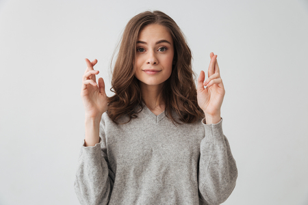 Smiling brunette woman in sweater praying with crossed fingers while looking at the camera over grey background Stock Photo