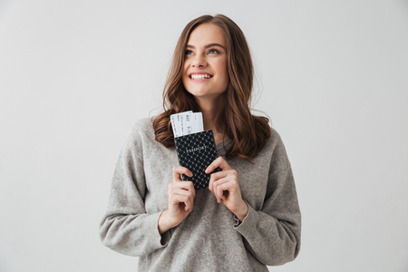 Happy brunette woman in sweater preparing to trip while holding passport with tickets and looking away over grey background