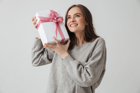 Smiling intrigued brunette woman in sweater holding gift box and looking up over grey background