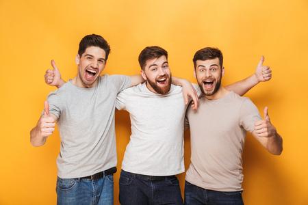 Drei junge aufgeregte Männer, die Daumen oben isoliert über gelbem Hintergrund zeigen