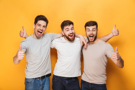 Trzech młodych mężczyzn podekscytowany pokazując kciuki do góry na białym tle na żółtym tle