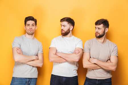 Two young upset men looking at their male friend isolated over yellow background Banque d'images - 103622053