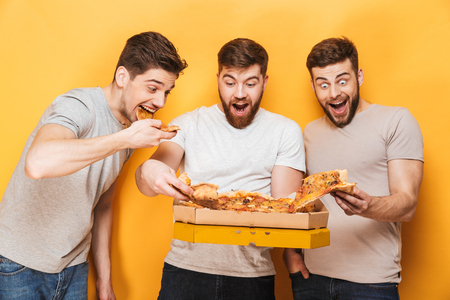 Three young cheerful men eating big pizza isolated over yellow background