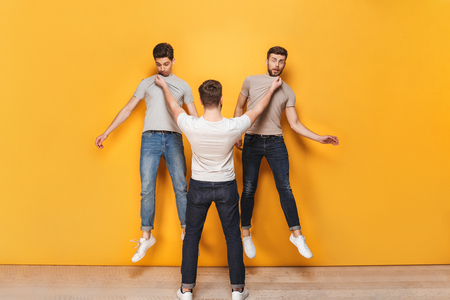 Angry man holding two other men by their collars isolated over yellow background Reklamní fotografie