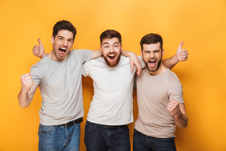 Three young excited men showing thumbs up and celebrating isolated over yellow background 版權商用圖片