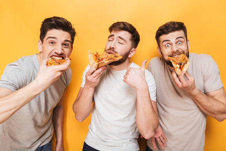 Three young delighted men eating pizza isolated over yellow background