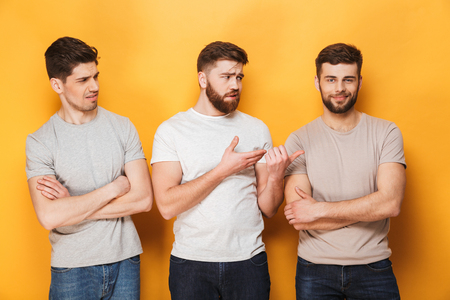 Two young upset men looking at their male friend isolated over yellow background Banque d'images - 103622097