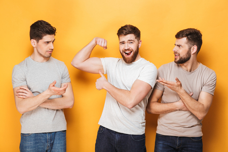 Two young envious men looking at their male friend isolated over yellow background Banque d'images - 103622099