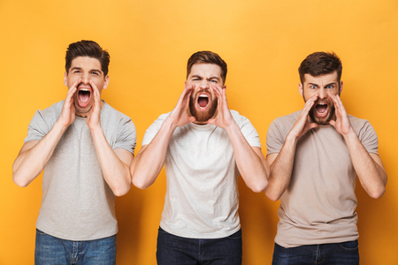 Three young angry men shouting isolated over yellow background 写真素材