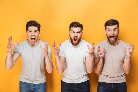 Three young angry men screaming isolated over yellow background