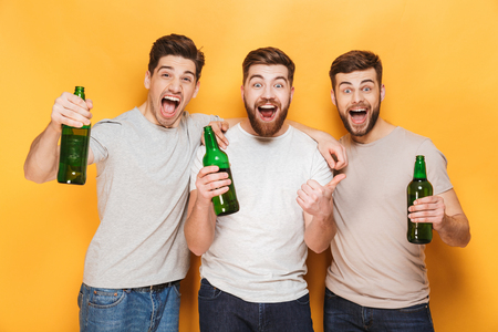 Three young happy men holding beer and celebrating isolated over yellow background Stock Photo