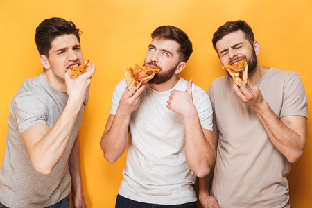 Three young smiling men eating pizza isolated over yellow background