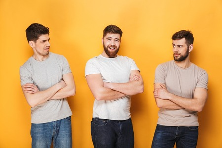 Two young suspicious men looking at their male friend isolated over yellow background