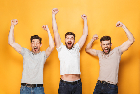 Three young excited men celebrating success and screaming isolated over yellow background