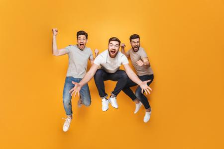 Drei junge aufgeregte Männer, die zusammen über gelbem Hintergrund springen Standard-Bild