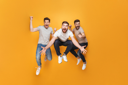 Three young excited men jumping together isolated over yellow background Stockfoto