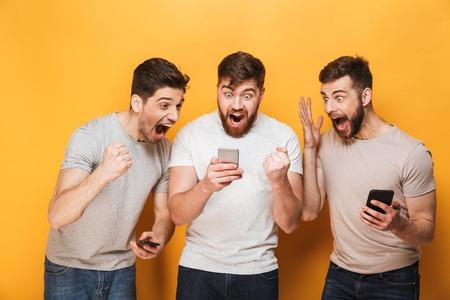 Trois jeunes hommes souriants regardant téléphone mobile et célébrant isolé sur fond jaune