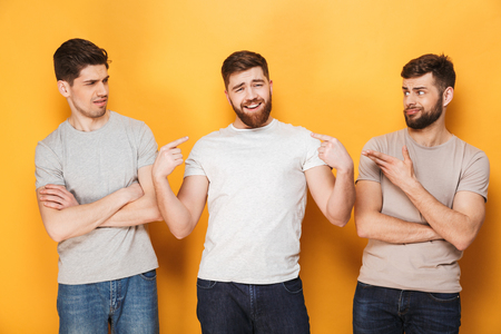 Two young confused men looking at their male friend isolated over yellow background