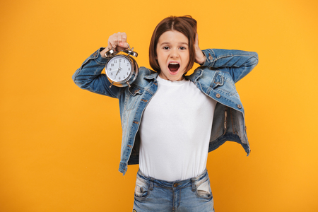 Portrait of a shocked little schoolgirl holding alarm clock over yellow background Stock Photo