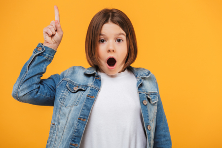Portrait of an excited little schoolgirl pointing finger up over yellow background