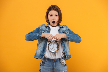 Portrait of an excited little schoolgirl holding alarm clock over yellow background