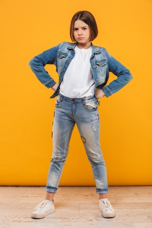Full length portrait of an upset little schoolgirl standing with hands on hips over yellow background Stock Photo
