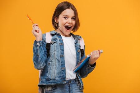 Portret van een opgewonden klein schoolmeisje die met rugzak een notitieboekje over gele achtergrond houden