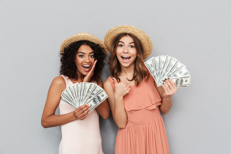 Portrait of two successful multiethnic women, caucasian and african american girls wearing straw hats holding fans of money 100 dollar banknotes isolated over gray background Stock Photo