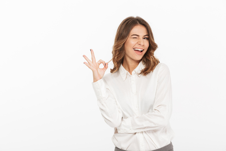 Portrait of a smiling young business woman looking at camera showing ok gesture isolated over white background