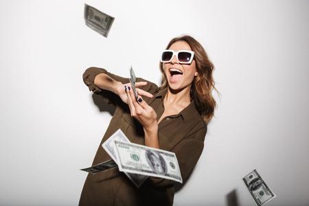 Portret van een gelukkige jonge vrouw die in zonnebril geldbankbiljetten weggooit die over witte achtergrond worden geïsoleerd
