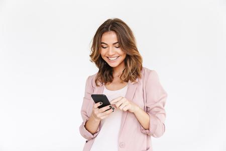 Imagen de la joven y bella dama linda que se encuentran aisladas sobre fondo de pared blanca mirando a un lado mediante teléfono móvil.