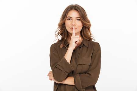 Portrait of a smiling young woman showing silence gesture isolated over white background Imagens