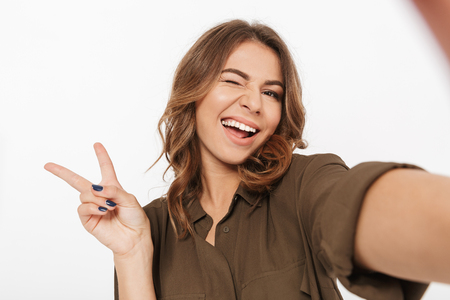 Portrait of a smiling young woman taking selfie with mobile phone isolated over white background