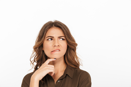 Portrait of a frustrated young woman looking away at copy space isolated over white background
