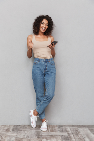 Full length portrait of a smiling young african woman holding mobile phone and showing thumbs up over gray background 스톡 콘텐츠