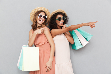Portrait of two lovely young women dressed in summer clothes holding shopping bags and pointing at copy space isolated over gray background