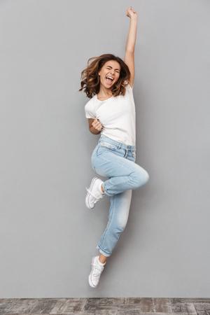 Ritratto integrale di una giovane donna allegra che salta e che celebra sopra fondo grigio