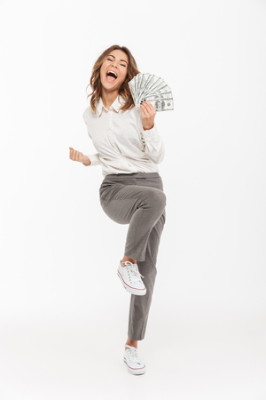 Full length portrait of an excited young business woman holding money banknotes and celebrating isolated over white background