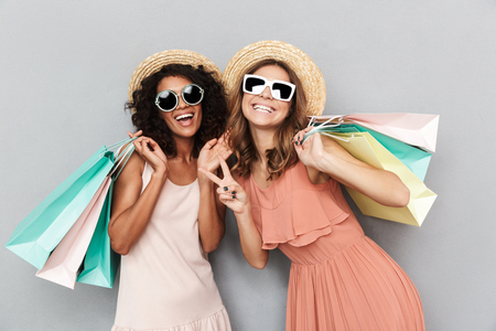 Portrait of two happy young women dressed in summer clothes holding shopping bags and showing peace gesture isolated over gray background