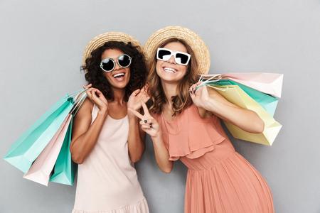 Retrato de dos mujeres jóvenes felices vestidas con ropa de verano sosteniendo bolsas de la compra y mostrando gesto de paz aislado sobre fondo gris