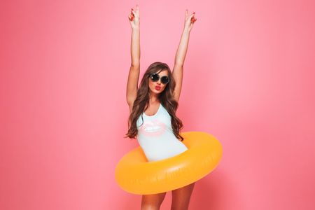 Portrait of an excited young woman dressed in swimsuit posing with inflatable ring isolated over pink background