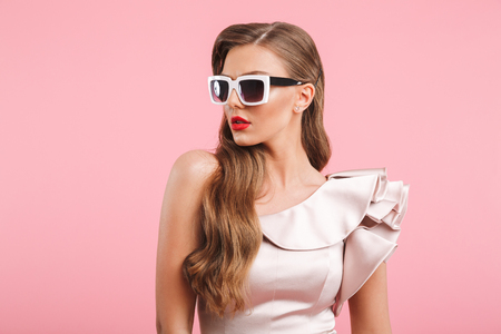 Portrait closeup of fashionable woman 20s in dress looking aside in stylish square sunglasses isolated over pink background Stock fotó